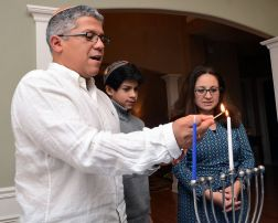 Schild, Scott. Yosef Spinoza lights his family's Hanukkah Menorah starting with the Shamash candle in the center, Wednesday at his home in Fayetteville. His son, Ari, 12, and wife, Zulma Tovar-Spinoza look on. 2013. Web. 19 Dec. 2014.