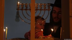 Ratner, Baz. An Ultra-Orthodox Jewish man holds a child as he lights a candle for the Jewish holiday of Hanukkah in Jerusalem's Mea Shearim neighbourhood. Hanukkah or Chanukah is the Jewish Festival of Lights. 2011. Web. 18 Dec. 2014.