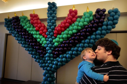Weber, Jim. Mark Cantora hugged his son Avi, 1 year old, near a menorah made out of balloons at the Chabad Center for Jewish Life in Memphis, Tenn., Dec. 9. 2012. Web. 18 Dec. 2014.