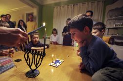 Joles, David. Henry Mrotz, 5 years old, right, watched as his mother lighted a menorah in Minneapolis on the first day of Hanukkah on Dec. 8. Observant Jewish people light a candle each night to mark the holiday. 2012. Web. 18 Dec. 2014.