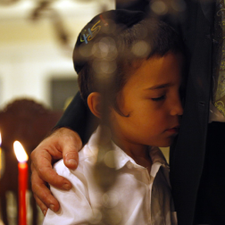 Cerri, Lara. A boy hugged his father after his family lighted candles in their St. Petersburg, Fla., home on Dec. 8. The holiday lasts eight days because according to tradition, when Jewish people rededicated a te. 2012. Web. 18 Dec. 2014.